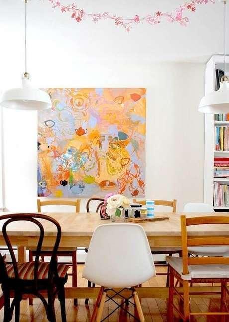 22. Quadros abstratos coloridos para delicada decoração de sala de jantar com mesa de madeira e várias cadeiras diferentes – Foto: Webcomunica