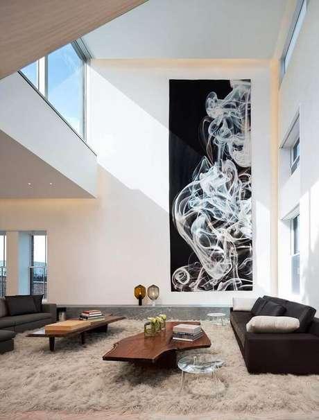 25. Decoração sofisticada para sala moderna com pé direito alto e quadro abstrato grande – Foto: Houzz