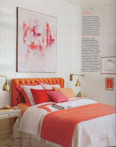 30. Quadro abstrato para decoração de quarto feminino com cabeceira laranja e arandela dourada – Foto: CoachDecor