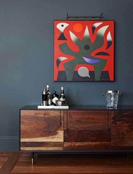 40. Quadro abstrato decorativo para parede preta com buffet de madeira – Foto: ProDesign
