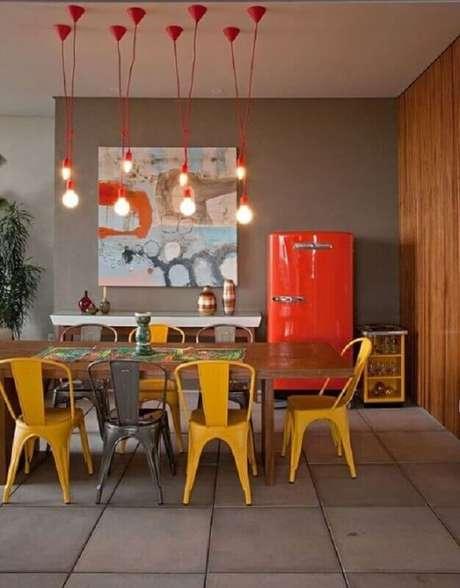 43. Quadro abstrato decorativo colorido para decoração de sala de jantar com cadeiras amarelas e pendentes vermelhos simples – Foto: Decoração e Ideias