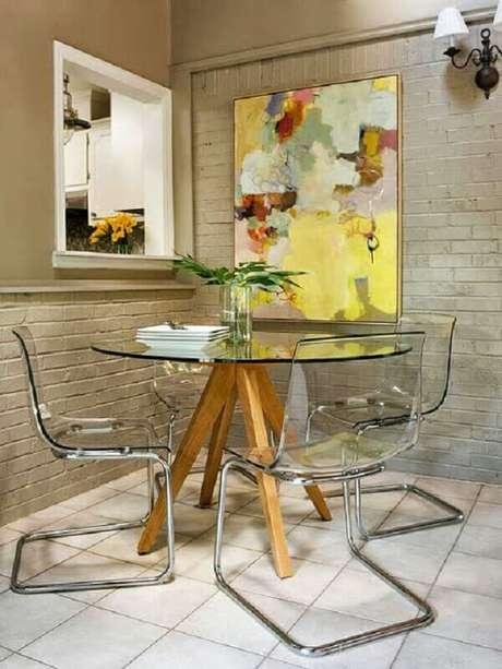 44. Quadros abstratos coloridos para decoração de sala de jantar com parede de tijolinho e mesa de vidro redonda – Foto: Pinterest
