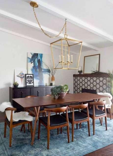 46. Quadros decorativos abstratos para decoração de sala de jantar com mesa de madeira e tapete azul – Foto: Pinterest