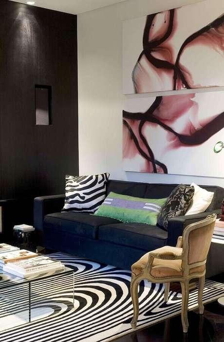 48. Quadros decorativos abstratos para sala simples decorada com tapete preto e branco e sofá azul escuro – Foto: Zize Zink Arquitetura