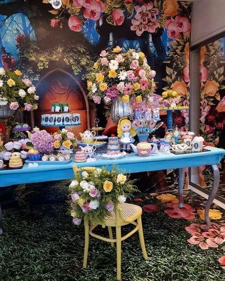 29. Decoração de festa Alice no País das Maravilhas com arranjo de flores coloridas e mesa azul – Foto: Pinterest