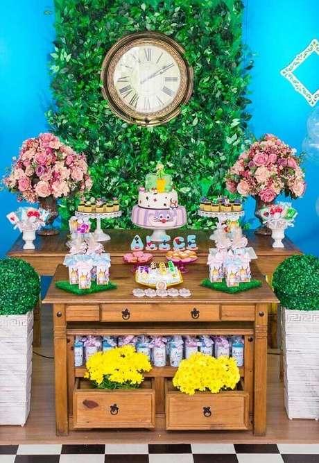 31. Decoração de festa Alice no País das Maravilhas simples com mesa de madeira e painel de folhagens com relógio antigo – Foto: Pinterest