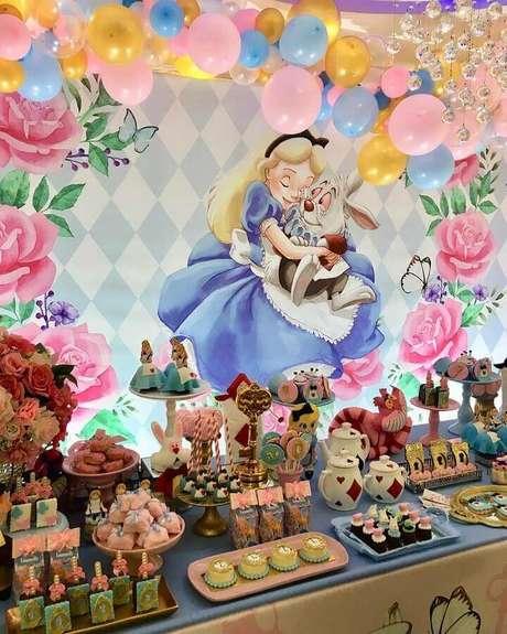 49. Painel decorado com arco de balões para festa Alice no País das Maravilhas com mesa repleta de doces personalizados – Foto: Kamila Barreira Festas