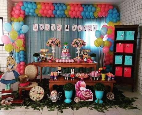 6. Balões coloridos e folhas embaixo da mesa para decoração de festa Alice no País das Maravilhas simples – Foto: Pinterest