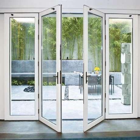 14. Área externa decorada com porta francesa de vidro com estrutura branca – Foto: Pinterest
