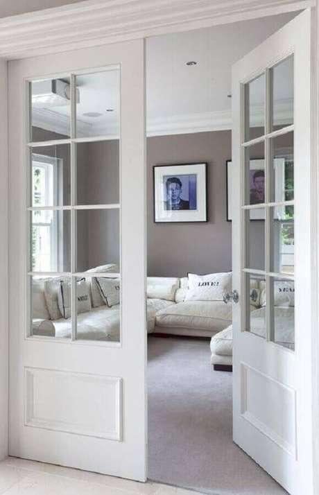 24. Decoração clean para sala com porta francesa branca – Foto: Revista VD