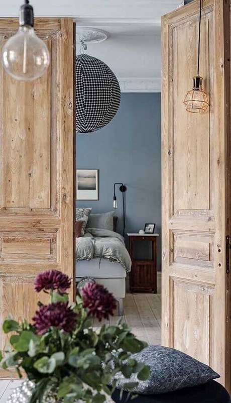 31. Decoração rústica com porta francesa de madeira para quarto – Foto: Architecture Art Designs