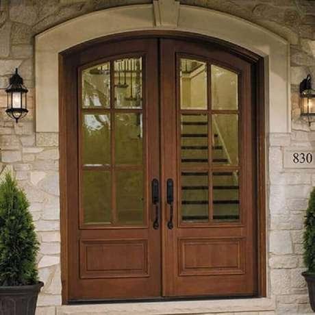34. Fachada com porta francesa de madeira e vidro com design clássico – Foto: Dream Exterior