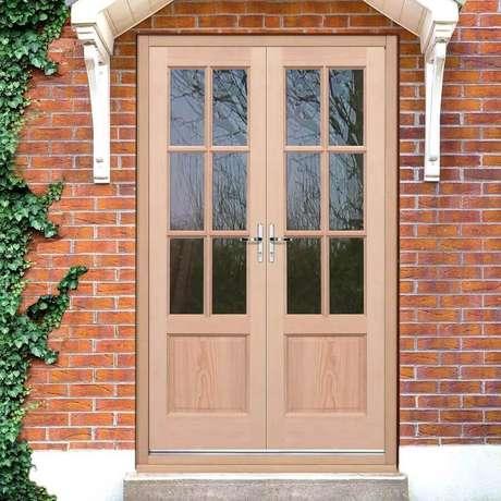 35. Fachada com tijolinho à vista e porta francesa de madeira com vidro – Foto: Carpinteria Rezende