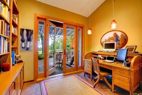 36. Home office decorado com porta francesa de madeira com saída para varanda – Foto: Webcomunica