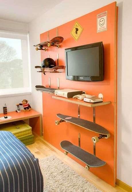 77. Quarto gamer decorado com painel laranja para TV e com suporte para apoiar skates – Foto: Pinterest