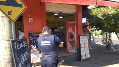 Guardas municipais notificam estabelecimento comercial sobre as regras do isolamento social, em Catanduva, interior de São Paulo