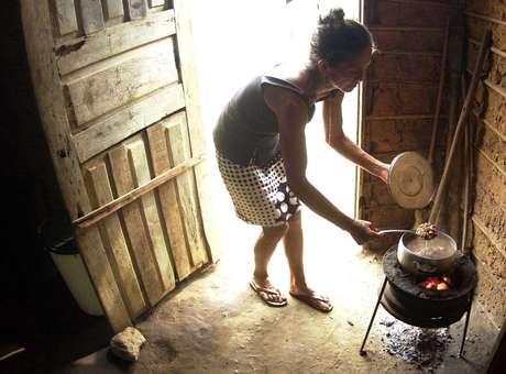 Mulher prepara comida em seu barraco, em favela localizada em Teresina, no Piauí. Foto: Roberto Castro / ESTADÃO.