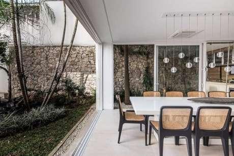 62. As pedras para jardim decoram a lateral da sala de jantar. Projeto de Catepoli