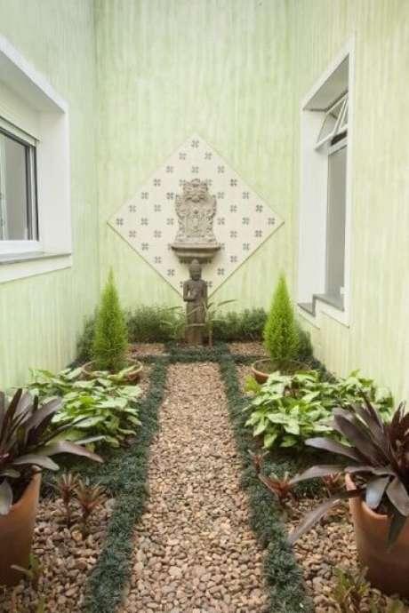 52. Jardim de inverno com chão de pedras e escultura oriental. Projeto de TT Interiores