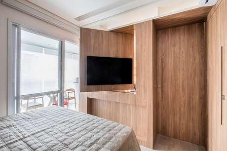 4. A marcenaria giratória é uma forma criativa de como esconder fios da tv pendurada na parede. Projeto por GoUp Arquitetura