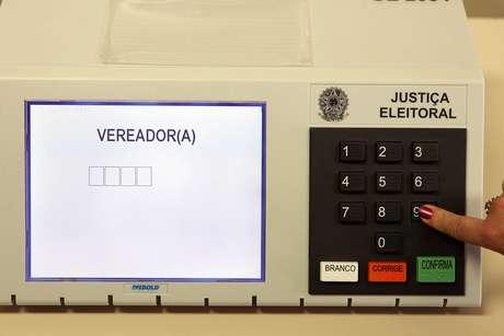 Funcionária do Tribunal Regional Eleitoral (TRE) junto a urna que está à disposição para o público na entrada do tribunal.