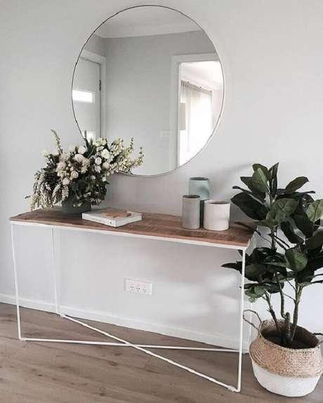 90. Espelho redondo e aparador de ferro complementa a decoração do espaço. Fonte: Pinterest