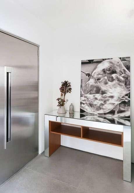 55. O aparador espelhado complementa a decoração da porta de entrada. Fonte: Pinterest