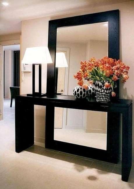 22. O aparador preto tem o mesmo acabamento da moldura do espelho. Fonte: Pinterest