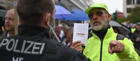 Homem mostra Constituição alemã a policial em protesto contra confinamento, em Frankfurt