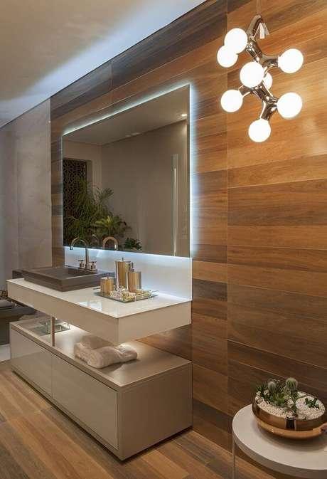 41. Banheiro com porcelanato amadeiro escuro e espelho iluminado ao redor – Via: Pinterest