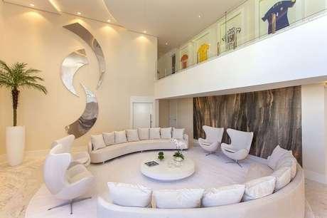 24. A escultura de parede espelhada foi fixada acima do sofá curvo neutro. Projeto por Iara Kilaris