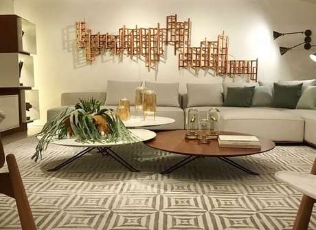 53. A escultura de parede metal dourada se destaca na sala de estar. Fonte: Dracena Home