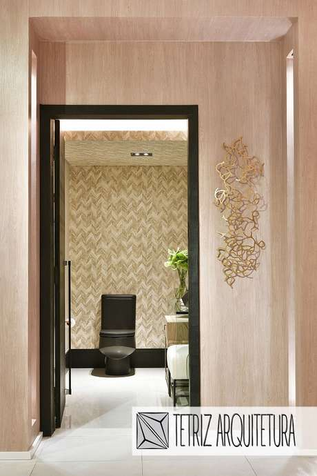 48. Entrada do lavabo com escultura de parede metal dourada. Projeto por Tetriz Arwuitetura e Interiores