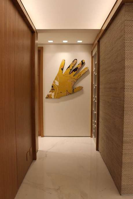 20. Escultura de parede feita com formato de mão amarela. Projeto por Maricy Marcos Borges