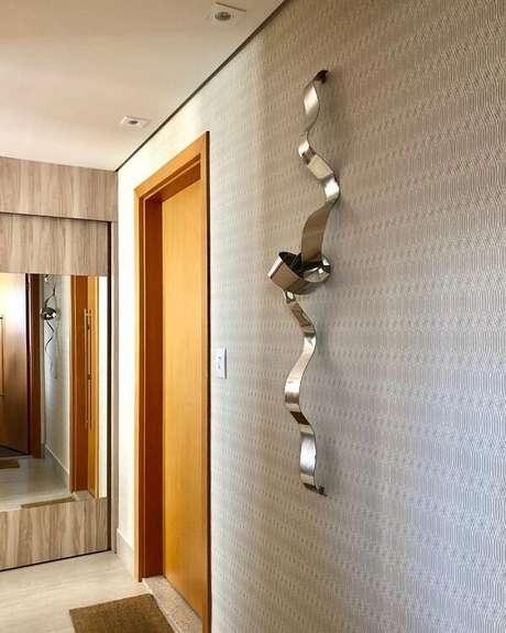 23. O hall de entrada ganhou movimento com essa escultura de ferro para parede. Fonte: Lu Abreu