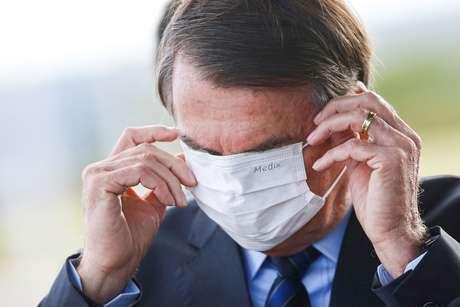 Presidente Jair Bolsonaro ajeita máscara na saída do Palácio da Alvorada 13/05/2020 REUTERS/Adriano Machado