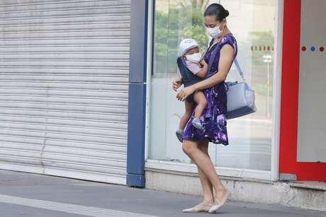 Mulher e criança usam máscaras e luvas como medida de proteção ao coronavírus, nesta quinta-feira, 26, na avenida Paulista