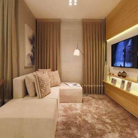 52. Sala pequena decorada na cor creme com painel de madeira e tapete felpudo – Foto: Sesso & Dazaneli Arquitetura