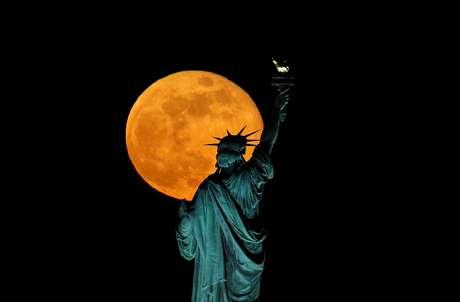 Vista da lua, em fenômeno conhecido como Super Lua, aparece atrás da Estátua da Liberdade, nos EUA.  7/5/2020. REUTERS/Brendan McDermid
