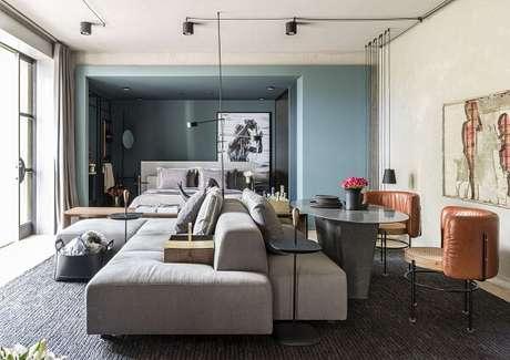 49. Sofá modular com tecido claro e poltronas de couro. Projeto por Hayasaki Arquitetura