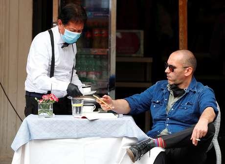 Homem é servido por garçom com máscara de proteção em restaurante de Roma 18/05/2020 REUTERS/Guglielmo Mangiapane