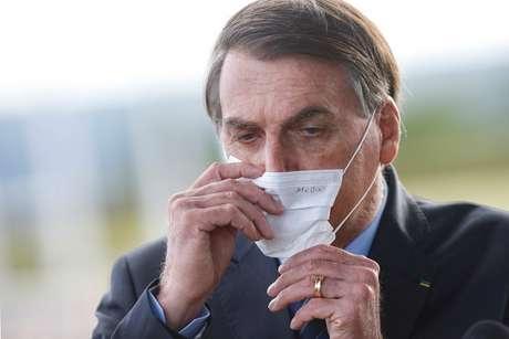 Bolsonaro ajusta máscara ao deixar Palácio da Alvorada 13/5/ 2020 REUTERS/Adriano Machado