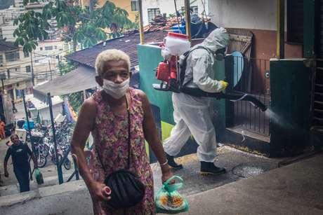 Moradores da comunidade do Santa Marta, zona sul do Rio de Janeiro, usando roupas de proteção, fazem higienização por conta própria na favela