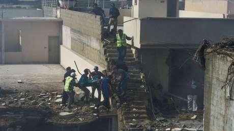 Residentes ajudam a retirar uma pessoa dos escombros; diversas casas foram destruídas