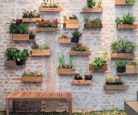 50. Esse jardim vertical ficou bem delicado com tantos vasinhos