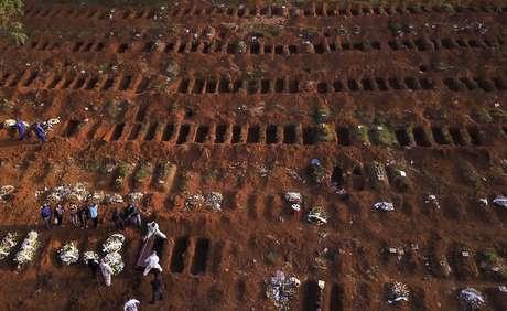 Sepultadores com trajes de proteção enterram vítima de Covid-19 no cemitério de Vila Formosa, em São Paulo 22/05/2020 REUTERS/Amanda Perobelli