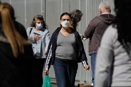 Movimentação de pedestres usando máscaras de proteção facial na Avenida Paulista durante o período de quarentena