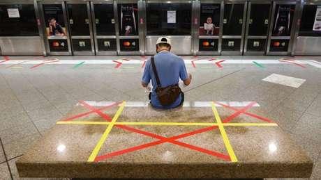 Homem sentado em um banco com marcações de distanciamento social
