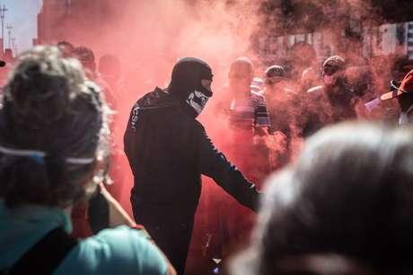 Um grupo de manifestantes pró-democracia, vestidos de pretos e usando máscaras, realiza um ato em frente ao Museu de Arte de São Paulo (Masp)