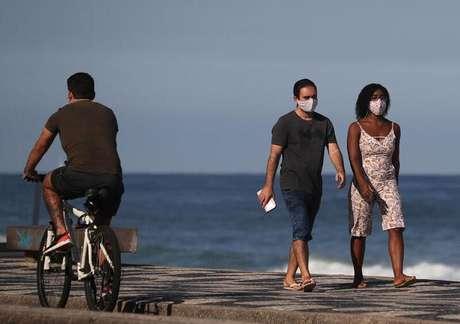 Casal com máscara de proteção caminha perto da praia do Leblon, no Rio de Janeiro 25/05/2020 REUTERS/Sergio Moraes